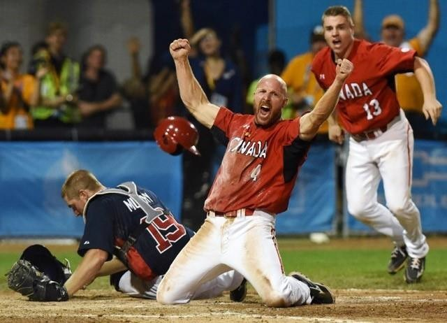 RYAN PFEIFFER / METROLAND - SPORT ACTION CATEGORY: Team Canada's Peter Orr celebrates after he knocked the ball loose from Team USA catcher Thomas Murphy to score the game winning run as Team Canada beat Team USA 7-6 in 10 innings to win the gold medal in men's baseball at the Toronto 2015 Pan Am Games at President's Choice Ajax Pan Am Ballpark on July 19, 2015. (CNW Group/News Photographers Association of Canada (NPAC))