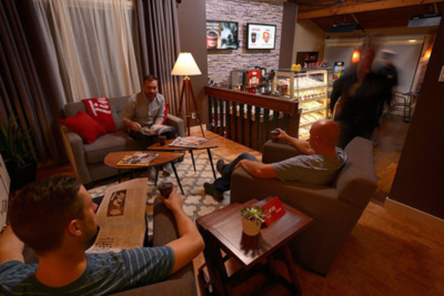 Les invités de Tim Hortons savourent le café préféré des gens d'ici au resto Tim de votre quartier à Calgary. Une résidence a été transformée en une nuit en un resto Tim Hortons de quartier pour lancer la nouvelle campagne de recrutement créative de l'entreprise. (Groupe CNW/Tim Hortons)