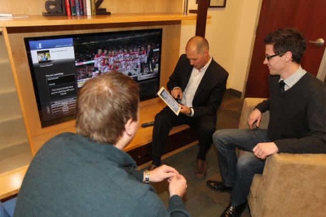 Andre LeBlanc, Bell Aliant, montre la nouvelle application Facebook pour le service Télé FibreOP(MC) à Mark MacMurtry et Anthony Murphy, employés de Bell Aliant (Groupe CNW/BELL ALIANT INC. - FRANCAIS)