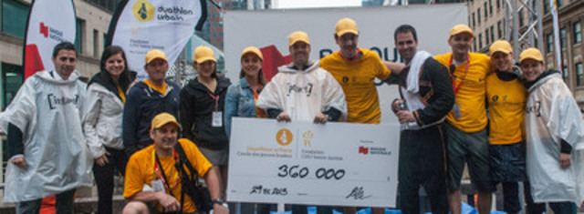 Goal exceeded! Canadian Olympic Champion and honorary chair of the race, Alexandre Bilodeau (left), and volunteers of the Urban Duathlon, presented by National Bank, unveiled the total of funds raised by the third edition of this event for Sainte-Justine UHC Foundation. (CNW Group/National Bank of Canada)