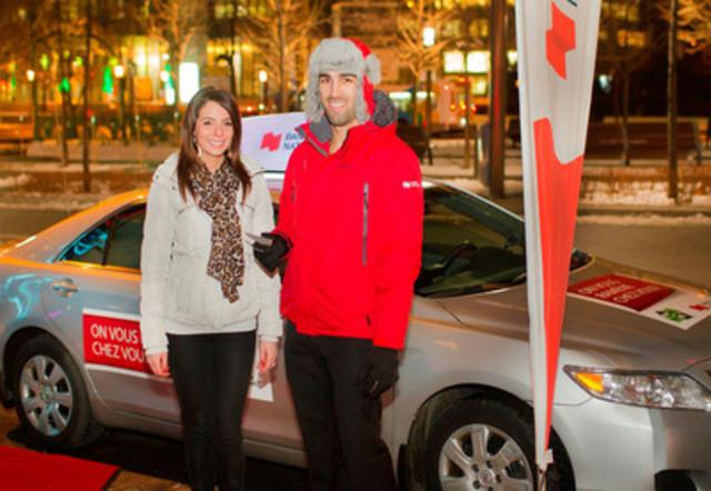 Un ambassadeur de la Banque Nationale offre des coupons Cool Taxi à une passante. (Groupe CNW/Banque Nationale du Canada)