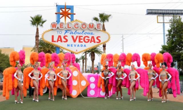 """In this photo provided by the Las Vegas News Bureau, Las Vegas breaks the Guinness World Record for the largest fuzzy dice on 11-11-11. The 4-foot pair of bright orange and pink dice are in front of the iconic """"Welcome to Fabulous Las Vegas"""" sign, and flanked by 11 """"Jubilee!"""" Showgirls from Bally's Las Vegas. (CNW Group/Las Vegas Convention and Visitors Authority)"""