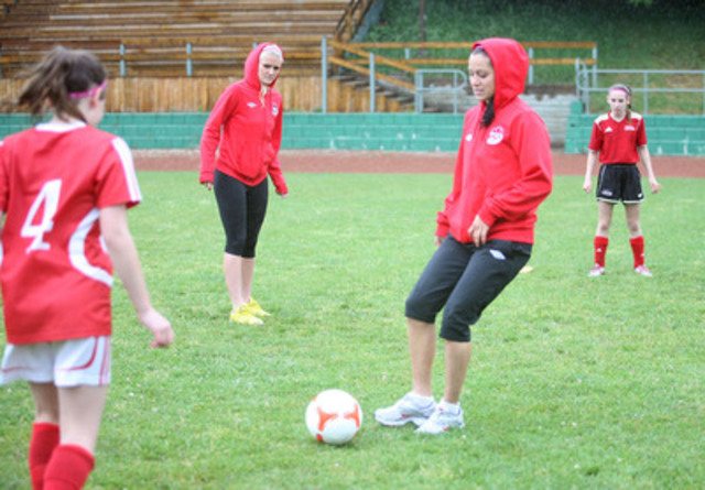 Members of Canada's Women's National Soccer Team and Toronto's U13 girls soccer team enjoy a fun practice in Toronto today. Wearing Because I am a Girl pink headbands and shoelaces, the teams demonstrate their support for girls' rights around the world, including girls' equal access to sports in developing countries. Proceeds from the sale of headbands and shoelaces will support a girls soccer project in Colombia. Pictured here (L-R) Kaylyn Kyle, Jonelle Filigno from the national team. (CNW Group/Plan Canada)