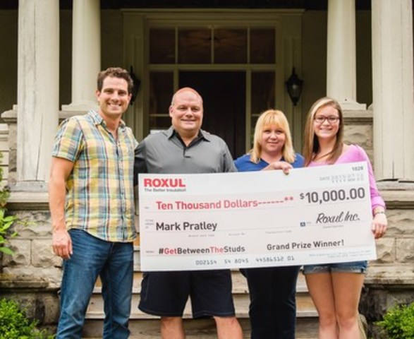 Scott McGillivray presents $10,000 cheque to ROXUL #GetBetweenTheStuds contest winner Mark Pratley and family. (CNW Group/Roxul Inc.)