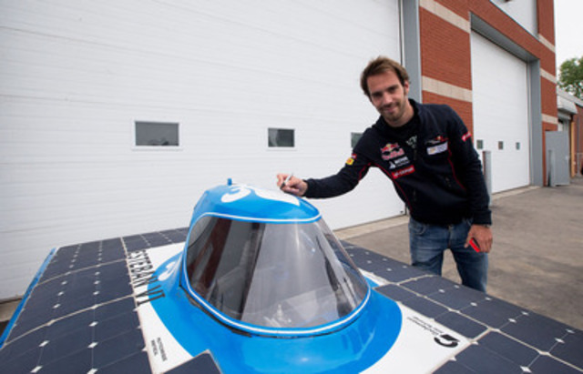 Formula One driver Jean-Eric Vergne poses for a photo as he signs an electric vehicle created by a Polytechnique Montréal student during the final stop of the 2013 AJAC Eco-Run event in Montreal on Thursday, June 6, 2013. (Michelle Siu for AJAC) (CNW Group/Automobile Journalists Association of Canada)