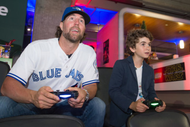 "Star Wars fan and videogame enthusiast R.A. Dickey of the Toronto Blue Jays plays the new LEGO Star Wars: The Force Awakens videogame on the main board at Rogers Centre with Émile Burbidge, Toys""R""Us Chief Play Officer, at the Canadian launch event yesterday. The game releases June 28. (CNW Group/Warner Bros. Interactive Entertainment)"