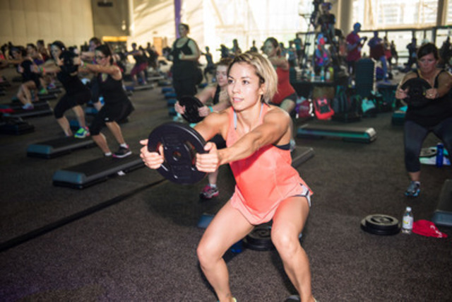 Participants squat with weight plates during a special Les Mills BodyPump class. Squats, lunges, deadlifts, rows, planks (aka hover) and push-ups are functional fitness exercises that encourage muscles to work together. Functional fitness was number two on canfitpro's Top 10 most effective fitness trends for 2015.  (CNW Group/Canadian Fitness Professionals Inc. (canfitpro))