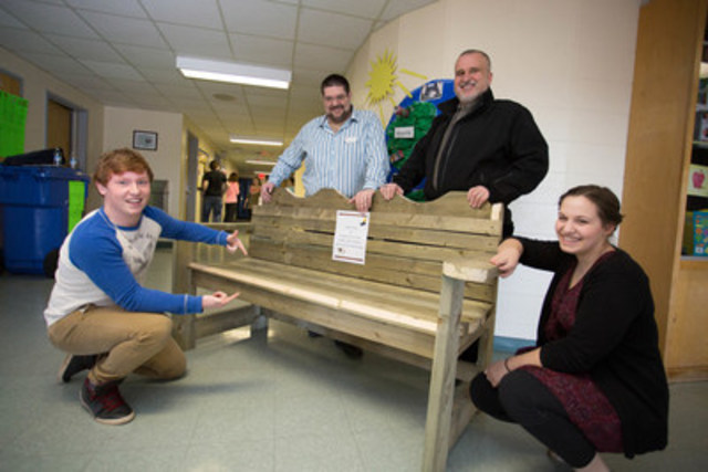 Cambridge-Narrows Community School's Grade 11 students, Cody Perry (left) and Emma Burke (right), show Christopher Dickson (left) and Rick Francioni (right) of Staples a bench they helped make for their outdoor classroom. For their eco efforts, the school won $25,000 worth of technology in the 2016 Staples Canada Superpower your School Contest. (CNW Group/Staples Canada Inc.)