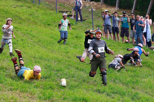 Ambitious Canadian cheese lovers chase after the 11-pound Courtenay Cheddar cheese wheel at the seventh edition of the Canadian Cheese Rolling Festival. (CNW Group/100% Canadian Milk)