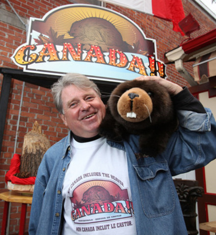 """MY CANADA INCLUDES THE BEAVER! BeaverTails Canada Inc. founder, Grant Hooker, leads the charge for preserving Canada's national symbol, the beaver. BeaverTails erected this eight-foot high """"monument"""" to the """"Ruler of the Wetlands"""" yesterday in the heart of the nation's capital. The """"monument"""" is, of course, a work in wood. (CNW Group/BeaverTails Canada Inc.)"""