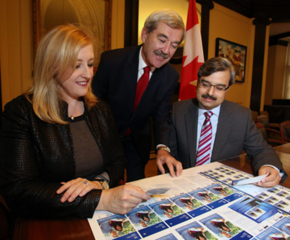 Canada Post President and CEO, Deepak Chopra (right), shows a new stamp featuring His Royal Highness Prince George to the Honourable Lisa Raitt, Minister of Transport and responsible for Canada Post, and Kevin MacLeod, Canadian Secretary to the Queen. The limited-edition commemorative stamp will be available starting October 22nd (CNW Group/Canada Post)