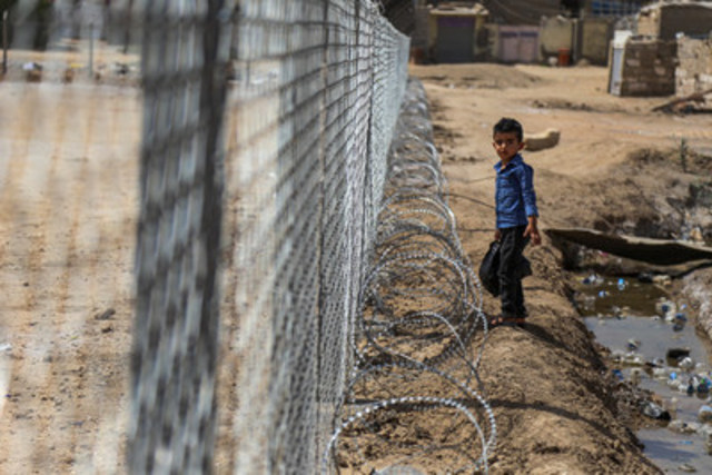 A young boy stands next to a fence surrounding the football field at Al-Shuhadaa Stadium in the city of ...
