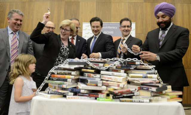 """Ministers Qualtrough and Bains took part in unlocking a chained pile of books representing unlocking access to literature for three million Canadians with print disabilities."" (CNW Group/CNIB)"