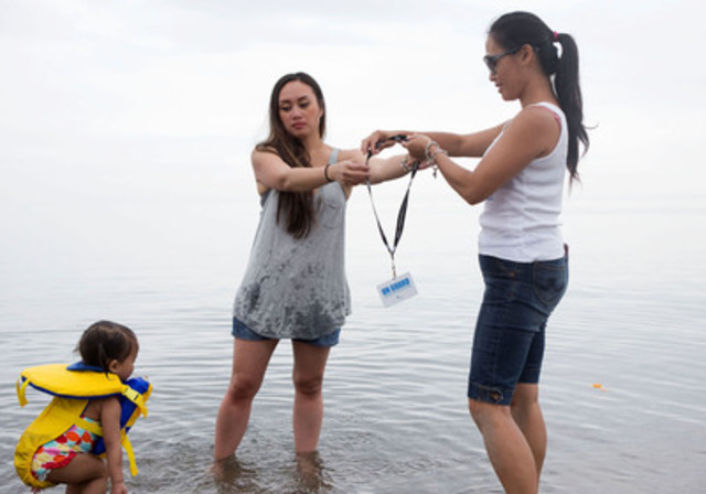 Nadia Luck passes her ON GUARD card to fellow mom Lala de Vera while keeping an eye on her daughter, during a Lifesaving Society water safety awareness event at Woodbine Beach in Toronto on Wednesday, June 25, 2014. (CNW Group/Lifesaving Society)