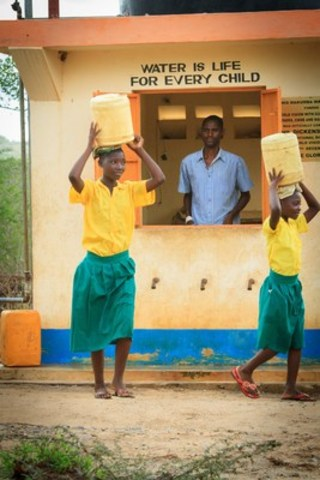 10-year-old Neema of Kenya (right) collects clean water with her sister from a water point World Vision built in her community. (CNW Group/World Vision Canada)