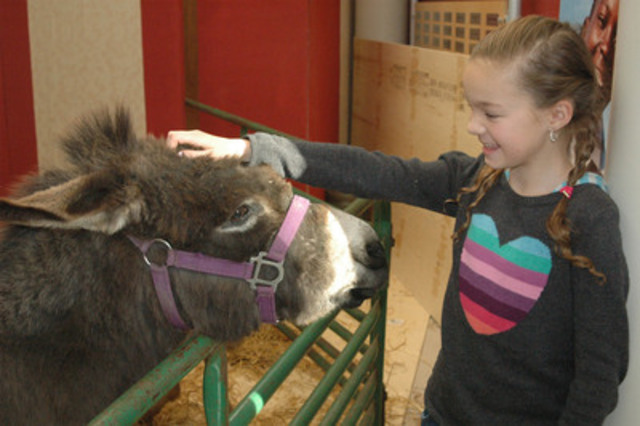 Madeline Carmichael, 10, poses with a donkey at a World Vision Gifts party, promoting their presents as a thoughtful last-minute holiday option. (CNW Group/World Vision Canada)