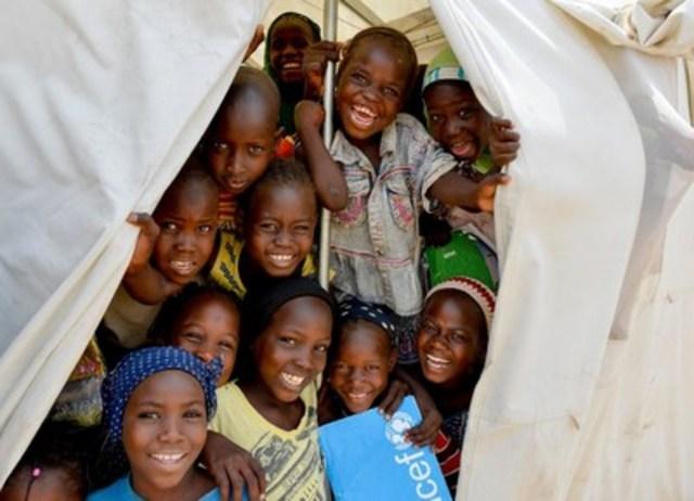 Des enfants sourient à l'entrée de leur salle de classe, une tente de l'UNICEF, dans un camp de réfugiés dans le nord-est du Nigeria. © UNICEF/UNI181989/Rich (Groupe CNW/UNICEF Canada)