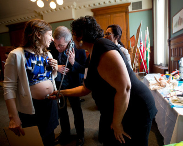 Midwife Manavi Handa holds a doppler to political staffer Lisa McDonald's belly as fellow staffer Don Jackson listens to the fetal heartbeat at the association's educational exhibit at Queen's Park in Toronto on Wednesday, March 6, 2013. MPPs had the opportunity to learn about the quality care provided to women and babies in Ontario. (Photo by : Michelle Siu) (CNW Group/Association of Ontario Midwives)