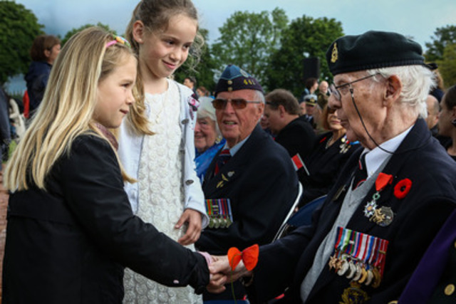 Canadian Veterans of the Battle of Normandy, Fraser Muir and Roy Eddy, receive poppies from French children as part of a ceremony at the Brettville-sur-Laize Canadian War Cemetery. Canada's Minister of Veterans Affairs, Julian Fantino, spoke on behalf of Canada. (CNW Group/Veterans Affairs Canada)