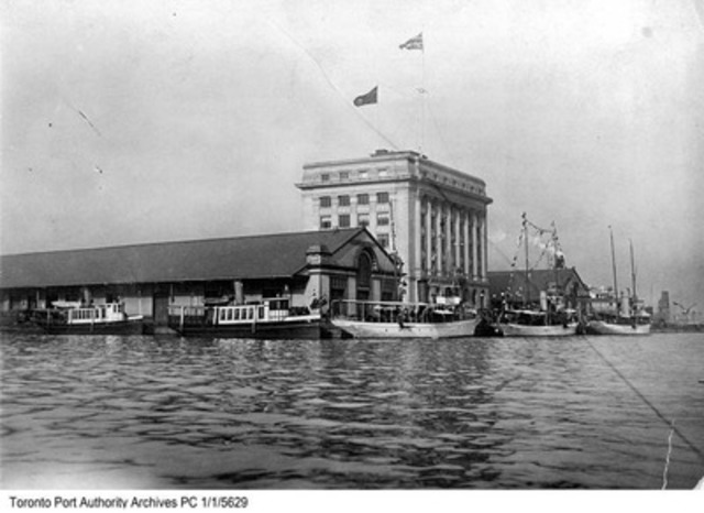 September 22, 1920: Photograph of steam yachts CLEOPATRA, BETHALMA and SEMARAMUS and R.C.Y.C. tenders KWASIND (nearest camera) and HIAWATHA tied up at Toronto Harbour Commission dock and east side of York Street Slip, in view looking north-east showing Canada St (CNW Group/Toronto Port Authority)