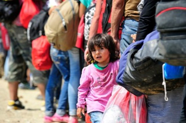 A young girl from Syria holds the hand of an adult while standing in a queue of people waiting to board a train to the border with Serbia, near the town of Gevgelija, on the Greek border. Since July, the rate of refugees and migrants transiting through the country has increased to approximately 2,000 to 3000 people per day, women and children accounting for nearly one third of arrivals. (CNW Group/UNICEF Canada)