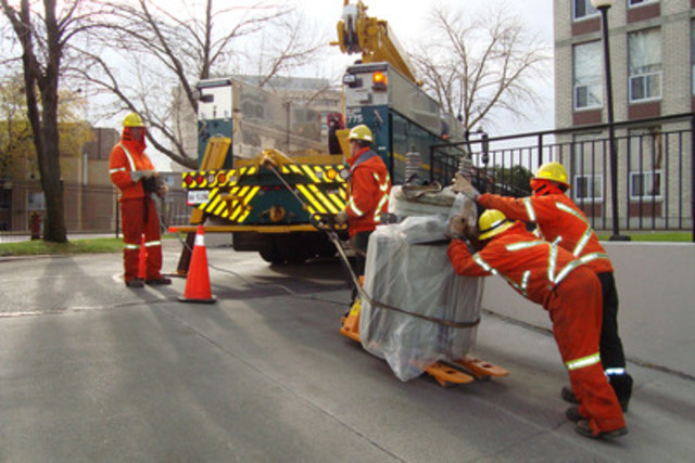 Toronto Hydro crews haul a 1,500 pound transformer into the underground garage at a 14-storey condo. With aging equipment causing 40 per cent of power outages in Toronto, this building is receiving three new transformers, at a cost of approximately $120,000, to improve the reliability of the electricity service to the premises. (CNW Group/Toronto Hydro Corporation)