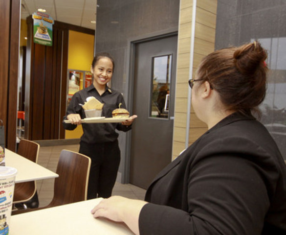 Crew Trainer Angel Soriano (L) delivers a custom built Create Your Taste burger at the McDonald's restaurant on 200th St. and 84th Ave. in Langley on Oct. 14, 2015. Metro Vancouver is the first region in British Columbia to roll out McDonald's Canada's new guest experience. (CNW Group/McDonald's Canada)