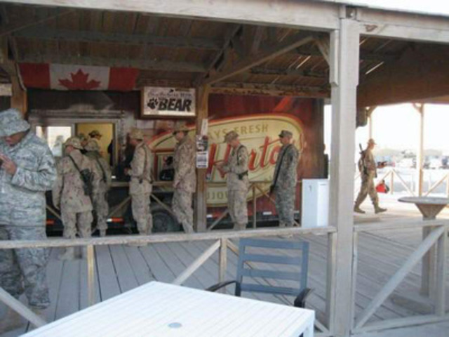 Soldats déployés à Kandahar, en Afghanistan, faisant la file devant la remorque Tim Hortons servant du café et des produits de boulangerie. Le 29 novembre 2011, après avoir servi 2,5 millions de clients de plus de 37 nationalités différentes en cinq ans, le Tim Hortons de la base d'opérations des Forces canadiennes à Kandahar, en Afghanistan, fermera ses portes. (Groupe CNW/Tim Hortons Inc.)