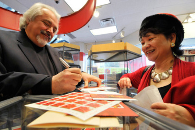 Today, Canada Post unveiled the Year of the Dragon stamps and collectibles in Toronto. Featured here is Louis Fishauf, designer of the stamp, providing an autograph to Rebecca Tam, Board Member of the Chinese Canadian National Council - Toronto Chapter. (CNW Group/Canada Post)