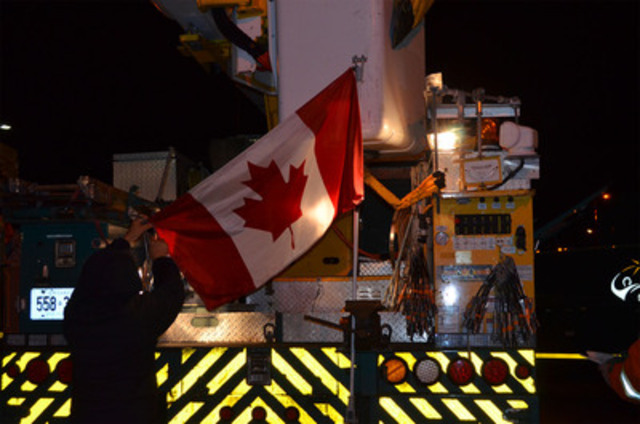 Stafford Higginson, an overhead cable line worker with Toronto Hydro affixes the Canadian flag to the rear of his bucket truck before leaving early this morning. Sixty-five Toronto Hydro employees left at 4 am -- one group heads to Sturbridge, Mass. and the other will go directly to Manhattan, NY. (CNW Group/Toronto Hydro Corporation)