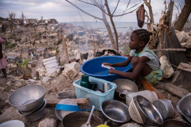 © UNICEF/UN038078/LeMoyne - Le 12 octobre 2016, Théogène, 8 ans, nettoie la vaisselle avec un peu d'eau à l'extérieur de sa maison détruite par l'ouragan Matthew à Jérémie, en Haïti. (Groupe CNW/UNICEF Canada)
