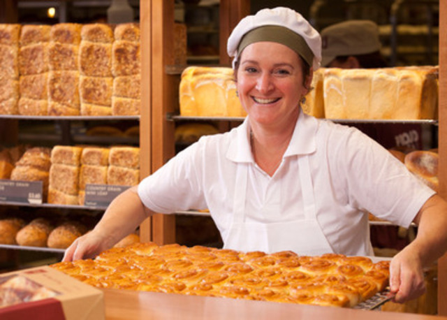 Co-owner Julia Turchet bringing out freshly baked cinnamon buns at COBS Grasslands in Regina. All baking is fresh every day and done at the bakery. COBS Grasslands was the first COBS to open in Regina last year and plans are underway for another location there in 2015. (CNW Group/COBS Bread)