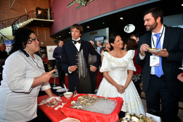 "Chef Ilona Daniel shucks and serves fresh Prince Edward Island oysters alongside the ""Father and Mother of Confederation"" for media and special guests in Toronto at the unveiling of the Official PEI 2014 Celebration Calendar. The province is inviting Canadians nationwide to be part of history by participating in these once-in-a-lifetime 2014 anniversary celebrations to commemorate the Charlottetown Conference - the event that led to the birth of Canada. (CNW Group/Prince Edward Island 2014 Inc.)"