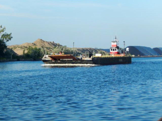 Photo : un remorqueur de McKeil pousse une barge transportant de l'équipement et des matériaux des terrains portuaires vers l'Aéroport Billy Bishop. Afin de réduire le trafic qui passe par le quartier de Bathurst Quay, l'équipement et les matériaux seront pour la plupart transportés jusqu'au site dans des barges à partir des terrains portuaires jusqu'à un quai temporaire, du côté est de l'aéroport. (Groupe CNW/PortsToronto)
