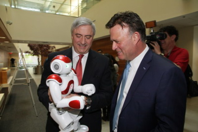 Dino Trevisani, president of IBM Canada, and Rob MacIsaac, president & CEO of Hamilton Health Sciences, interact with Pepper the Robot, powered by IBM Watson, at the announcement of the IBM and Hamilton Health Sciences innovation initiative. (CNW Group/IBM Canada Ltd.)