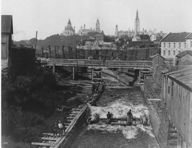 View from the Chaudière Falls generating station on the Ottawa River, with Parliament of Canada in the ...