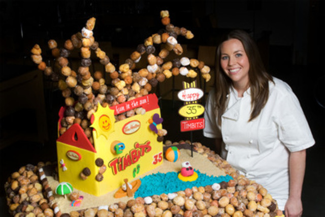 Chef Andrea Nicholson, of Top Chef Canada, with the Tim Hortons Timbits cake she created to celebrate the Timbits' 35th birthday. Nearly four feet tall, the cake contains more than 1,500 Timbits and features a replica of the Timbits box and Timbits enjoying summer activities. (CNW Group/Tim Hortons Inc.)
