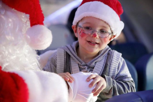Air Transat et la Fondation Rêves d'enfants ont emmené aujourd'hui des centaines d'enfants vers le pôle Nord, au départ de Montréal Toronto et Calgary, pour ramener le père Noël. Sur la photo : le père Noël et un enfant parrainé par la Fondation. (Groupe CNW/Transat A.T. inc.)