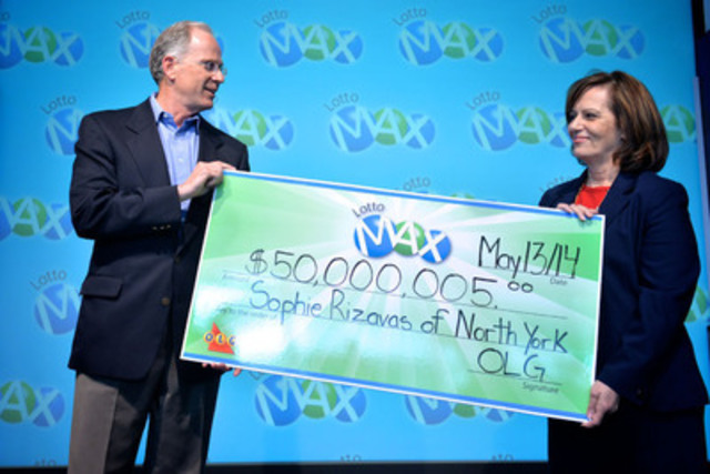 OLG's Executive Director of Lottery Marketing John Mahony presents Toronto resident Sophie Rizavas with a cheque for $50,000,020 at the OLG Prize Centre Tuesday. Sophie won the May 9, 2014 LOTTO MAX jackpot. Credit: Shan Qiao (CNW Group/OLG Winners)
