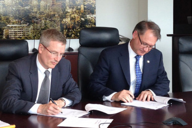 Xavier Lancksweirt, General Manager at Solvay Business Services, and George D. Schindler, President and Chief Executive Officer of CGI, sign the contract in Montréal (CNW Group/CGI Group Inc.)