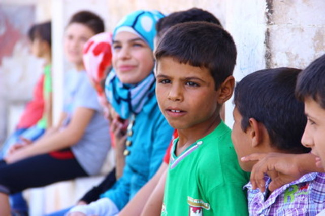 """On September 13, 2015 in the Syrian Arab Republic, Hasan (in green shirt), with some of his friends, watches other children (not pictured) leave their school at the end of the first day of classes. The boys, who are displaced from Wedaihey Village, near Aleppo, have dropped out of school. After seeing the other children at school, Hassan wants to be with them. """"I miss school,"""" he said. """"I want to go back and be like other kids."""" (Photo credit: © UNICEF/UNI198165/Al-Issa) (CNW Group/UNICEF Canada)"""