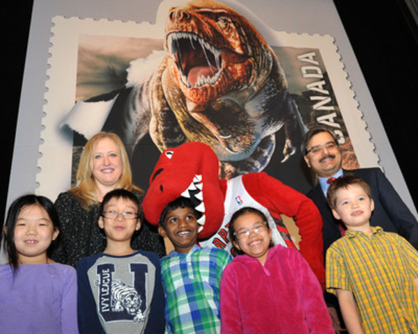 Canada Post today unveiled a new stamp issue - Dinos of Canada - featuring prehistoric animals that once roamed Canada. In the image, the Honourable Lisa Raitt, Minister of Transport, Deepak Chopra, President and CEO, Canada Post, the Toronto Raptor and students from Jesse Ketchum Public School  (CNW Group/Canada Post)