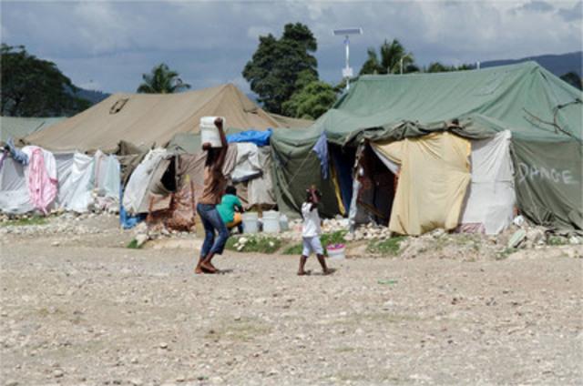Jacmel, Haïti : Une femme transporte un seau d'eau depuis le point de distribution d'eau de Save the Children jusqu'à sa tente, au camp Pechinat, à Jacmel, dans le sud-est d'Haïti. Le tremblement de terre, qui a entraîné le déplacement de millions de personnes, a laissé les enfants dans une situation très précaire. (Groupe CNW/IKEA Canada)