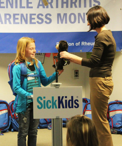 9-year-old Aaliyah Hester talks about her new backpack and bear with The Arthritis Society's Kelly Morphet (CNW Group/The Arthritis Society)