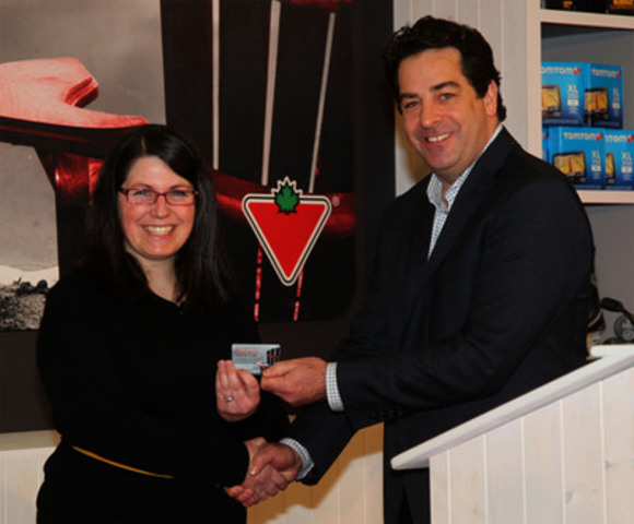 Rob Shields of Canadian Tire hands the first Canadian Tire 'Money' Advantage card to Nancy Stapleton of Adsum for Women and Children in Halifax. Ranked among the best in Canada, the program offers a powerful fundraising tool for eligible local community groups. The pilot will run in Nova Scotia only starting February 24. (CNW Group/CANADIAN TIRE CORPORATION, LIMITED)