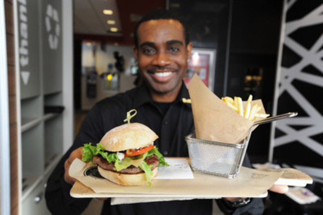 A server-one of three new positions at McDonald's Canada delivers a custom burger from the new Create Your ...