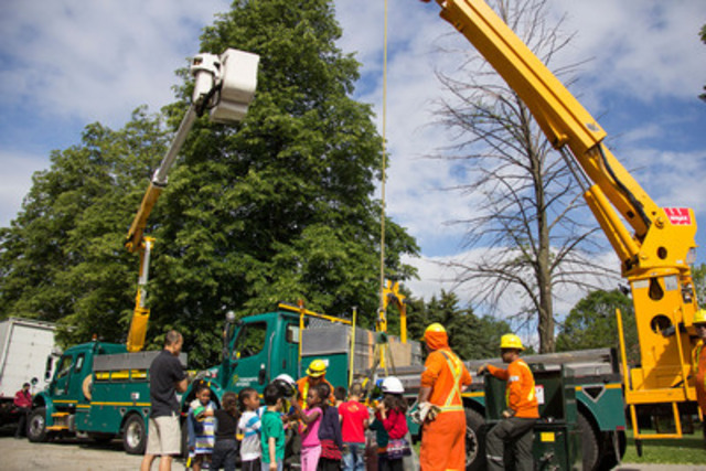 Kids at Ryerson Community School examine a bucket truck while learning about electrical safety from Toronto Hydro crew members. (CNW Group/Toronto Hydro Corporation)