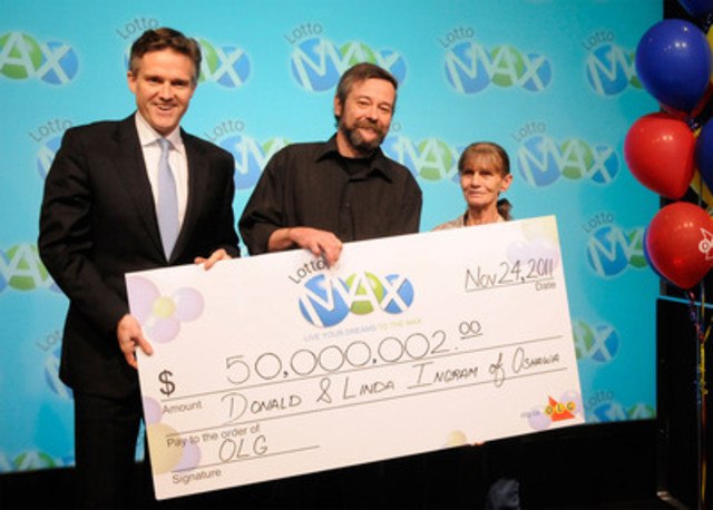 President and CEO of OLG Rod Phillips, left, presents Oshawa couple, Don and Linda Ingram, with a cheque for $50 million at the OLG Prize Centre Thursday. The Ingrams won the LOTTO MAX jackpot prize after purchasing a ticket for the November 18 draw. (CNW Group/OLG Winners)
