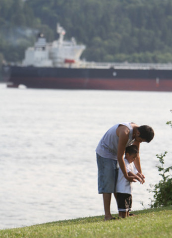 Robbie George and his son, Cassius, of Tsleil-Waututh Nation, stand along the shores of Burrard Inlet prior to the Nation's signing of the Save the Fraser Declaration. Photo by James Maclennan (CNW Group/Tsleil-Waututh Nation)