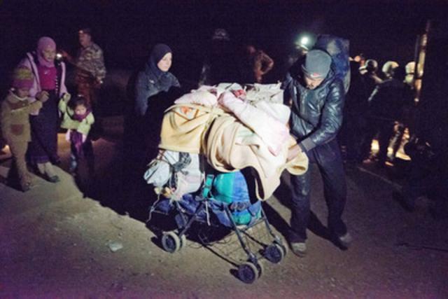 Jordanie / Cet homme et sa femme utilisent une poussette pour transporter leurs effets au-delà de la frontière. La plupart des réfugiés arrivent à partir de la ville avoisinante Dara'a qui se trouve au sud de la Syrie ou des villages alentours. (Groupe CNW/HAUT COMMISSARIAT DES NATIONS UNIES POUR LES REFUGIES)